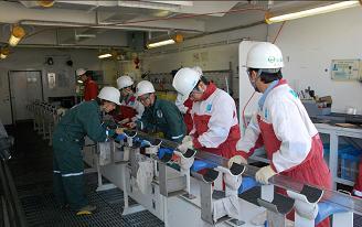 Christine Destrigneville (à gauche) sélectionne un fragment de carotte pour en analyser les sédiments. Crédit : Japan Agency for Marine Earth-Science Technology / Integrated Ocean Drilling Program